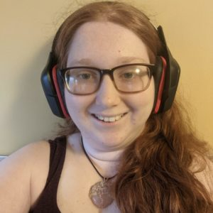 A picture of Hannah, a red-headed woman with black and red headphones, a crystal necklace, and a purple shirt.